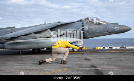 A U.S. Navy Senior Chief Aviation Boatswains Mate Cedric Williams signals to the pilot of an AV-8B Harrier II fighter jet for take off from the flight deck of the USS Boxer during operations November 23, 2019 in the Pacific Ocean. - Stock Photo