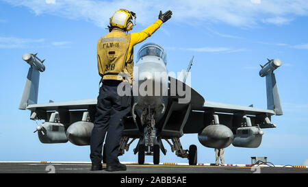 U.S. Navy Aviation Boatswains Mate 3rd Class Derek Riley signals to the pilot of an E/A-18G Growler Electronic fighter jet for take off from the flight deck of the Nimitz-class aircraft carrier USS Theodore Roosevelt during operations November 22, 2019 in the Eastern Pacific Ocean. - Stock Photo