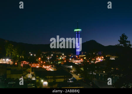 Gatlinburg Space Needle illuminated with neon, vibrant downtown bustling with tourists, Great Smoky Mountains National Park in distance, Tennesse, USA - Stock Photo