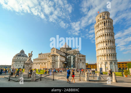 Tourists fill the Field of Miracles and Cathedral square alongside the Leaning Tower, Baptistery and Duomo in the Tuscan city of Pisa, Italy - Stock Photo