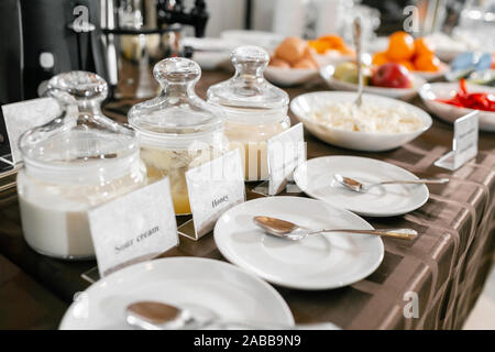 Saucers with spoons in the foreground. Honey, condensed milk, yogurt. Breakfast buffet in hotel. - Stock Photo
