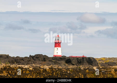 Longstone Lighthouse in white and red, on Longstone Rock in the outer group of the Farne Islands off the Northumberland Coast - Stock Photo