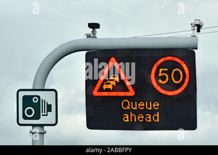 Single panel M25 motorway sign above lane one 50MPH variable speed limit & Queue Ahead message complete with CCTV cameras & standard camera sign UK - Stock Photo