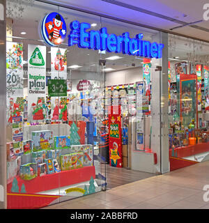The Entertainer retail toy shop front window display & business brand sign above entrance to Lakeside shopping centre store in Intu shopping mall UK - Stock Photo