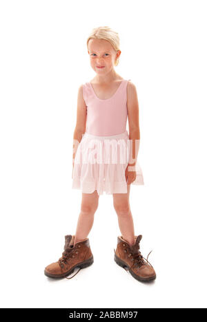 Young blonde girl dressing up in ballet outfit and Dad's big walking boots - Stock Photo