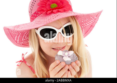 Beautiful young blonde girl in big pink floppy hat and white framed sunglasses holding a cup cake up to her face. White studio background - Stock Photo