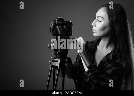 Studio shot of young beautiful hipster woman vlogging in black and white - Stock Photo