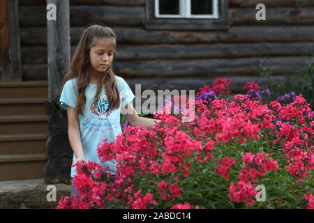 Girl near the flowers - Stock Photo