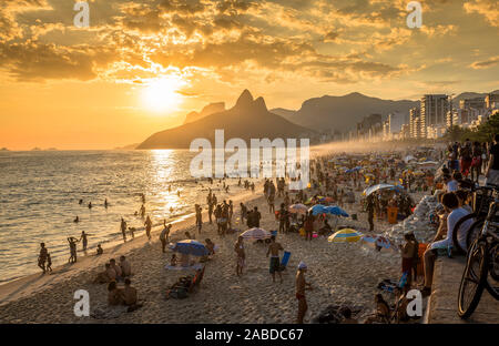 RIO DE JANEIRO, BRAZIL - FEBRUARY  2016: People watching sunset on iconic Ipanema Beach in Rio de Janeiro. Rio will host 2016 Summer Olympic Games. - Stock Photo
