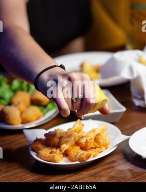 man squeezing lemon on top of the crispy fried cheese - Stock Photo