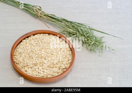Oatmeal in a brown ceramic bowl with on a background of green ripe ears of oats on a linen tablecloth. The concept of cooking natural healthy food. - Stock Photo