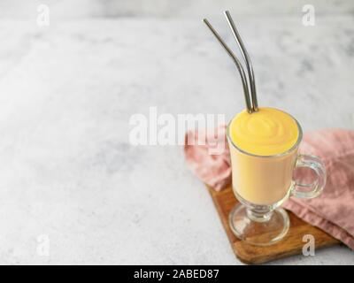 Yellow mango yogurt or smoothie on gray cement background with copy space left. Turmeric Lassie or lassi in glass with metal straws - Stock Photo