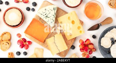 An assortment of cheeses panorama, shot from above on a white background. Blue cheese, soft cheese and other sorts with fruit and nuts, wine and grapes - Stock Photo