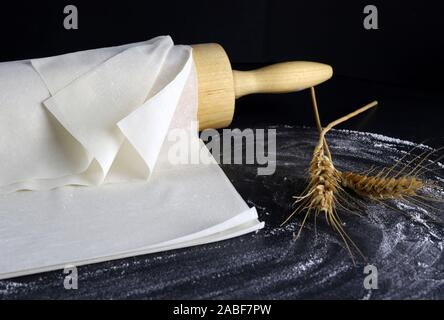 Closeup of phyllo dough on a floured table. Dark background with rolling pin and ears of wheat. - Stock Photo