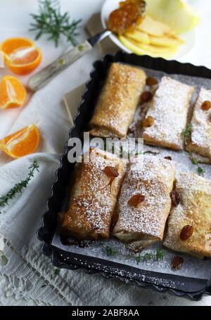 Top view of homemade phyllo dough rolls with apples and orange marmalade. White background with sultanas. - Stock Photo
