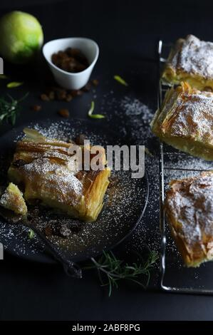 Concept of Greek cuisine. Homemade traditional greek Bougatsa, phyllo pastry filled with cream and sultanas on dark background.Top view - Stock Photo