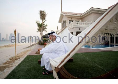 Saif, 26 year old half Emirati half American who runs his own company in Abu Dhabi is sitting in the garden of his house on Palm Island. - Stock Photo