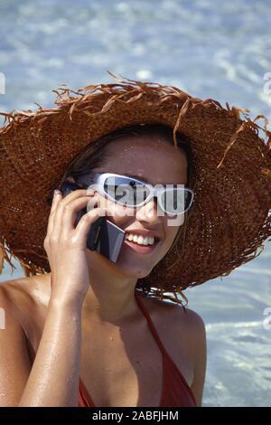 Portraet einer jungen Frau mit Sonnenhut, Sonnenbrille und Handy Stock Photo