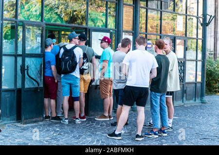 Budapest, Hungary - September 13, 2019: People queuing in front of museum building. Waiting for a ticket purchase - Stock Photo