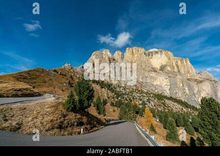 The winding road through the beautiful landscape at the Sella mountains pass in South Tyrol, Italy on a sunny autumn day - Stock Photo