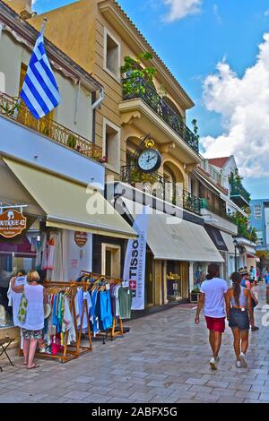 A view along Lithostroto, the main shopping street in the centre of the capital town, Argostoli. Young couple in shorts walking by. - Stock Photo
