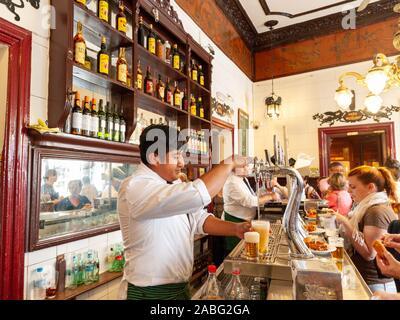 Hispanic barman pouring beer at Bar Casa Labra, Madrid, Spain - Stock Photo