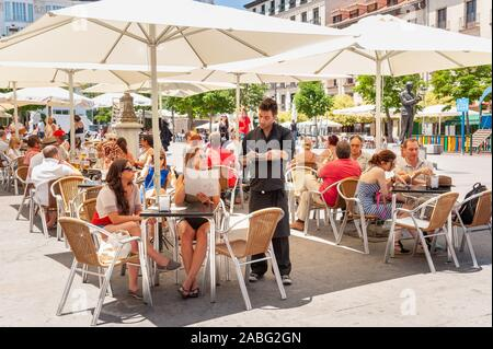 People ordering drinks at bar tables on Plaza de Santa Ana, Barrio de las Letras, Madrid, Spain - Stock Photo