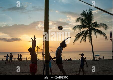 18.11.2019, Phuket, Thailand, Asia - A group of locals plays volleyball in the sunset on Karon Beach. - Stock Photo