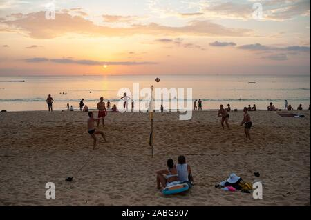 18.11.2019, Phuket, Thailand, Asia - A group of tourists plays volleyball in the sunset on Karon Beach. - Stock Photo