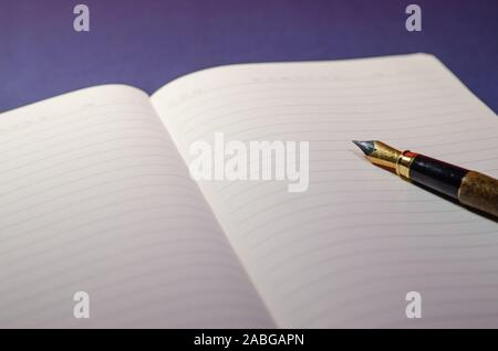 Close view of the tip of a pen writing on an open agenda or notebook with blank pages. Writing on paper with pen ink. Blue surface, wallpaper or deskt - Stock Photo
