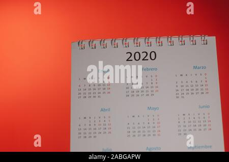 New Year 2020 calendar on desk, red illuminated background. Planning, organizing the new year, months of the new year. Close up view of the object wit - Stock Photo