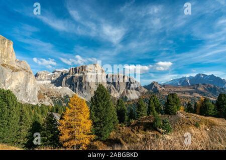 The Sass Pordoi mountain of the Sella massif on a bright autumn day with yellow coloured trees in the italian Dolomites - Stock Photo
