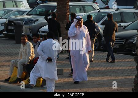 Kuwaiti man in traditional white robe (dishdasha) talking on the phone with Asian expatriates around him on the sidewalk - Stock Photo