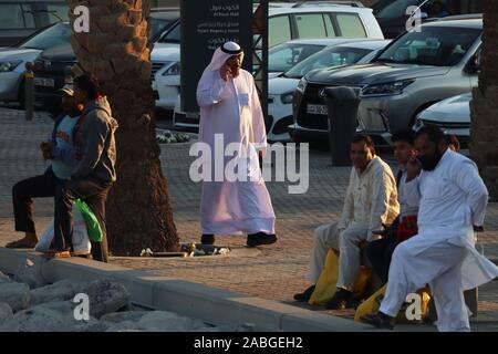 Kuwaiti man in traditional white robe (dishdasha) talking on the phone with Asian expatriates around him on the sidewalk - Stock Photo