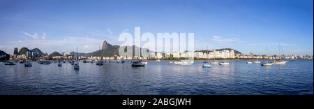 Wide panorama view of Rio de Janeiro at sunrise with the Corcovado mountain in the background and pleasure boats scattered in the Guanabara bay - Stock Photo
