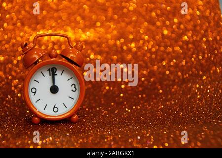 Golden clock to the left of the photo showing midnight on a golden background with a glitter. Copy space for advertising. Copy space area for text.