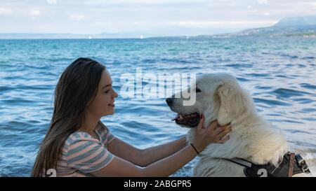 Smiling young woman with light brown hair is holding a large white dog on a blurred background of blue lake and mountains. - Stock Photo