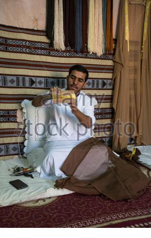 United Arab Emirates - Abu Dhabi - An Iraqi artisan specilized in hand made Bisht, the traditional overcoat worn by Emirati men in formal social occasions. - Stock Photo