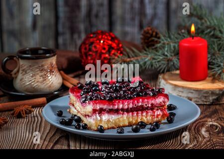 Slice of Christmas cheesecake with blackcurrant filling on a rustic wooden table - Stock Photo