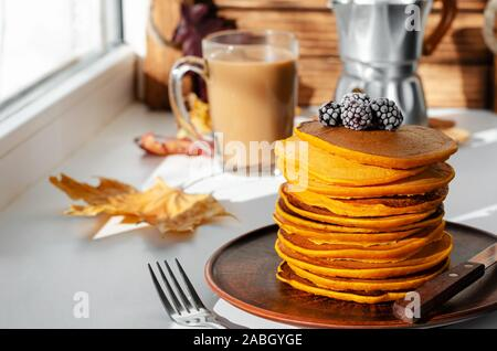 A heap of pumpkin pancakes with blackberries. Delicious breakfast. - Stock Photo