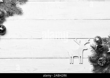 Winter time concept. Deer made of wood put in corner near decorated fir tree branches. Composition of Christmas tree decor, copy space. Christmas decorations on white wooden texture background. - Stock Photo