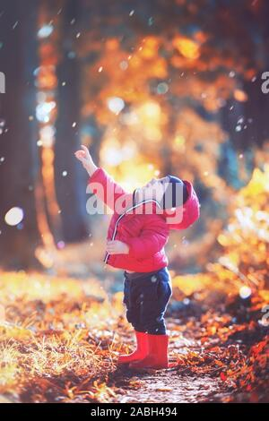 Little toddler boy in red rubber boots and red jacket catching drops of rain in autumn park. Orange forest leaves on background Stock Photo