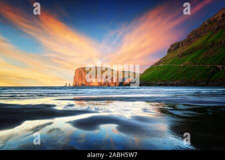 Incredible sunset in low tide time on Atlantic ocean coast near village Tjornuvik. Famous rock formations Risin and Kellingin Eidiskollur on background. Faroe Islands, Denmark. Landscape photography - Stock Photo