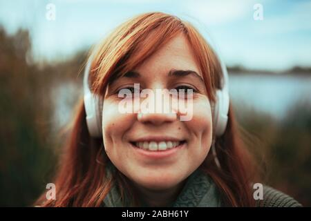Young woman taking a selfie with her smartphone near a lake and headphones - Stock Photo