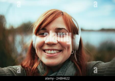 Young woman taking a selfie with her smartphone near a lake and headphones
