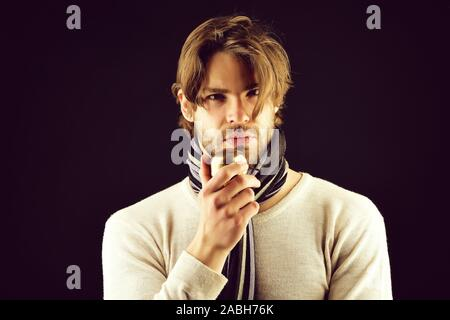 Man with beard and attentive look wears striped scarf and holds golden apple as symbol of ownership. Isolated on black background. Concept of confidence - Stock Photo