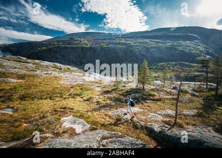 Kinsarvik, Hordaland, Norway. Young Woman Lady Tourist Traveler Backpacker Hiking In Hardangervidda Mountain Plateau. Famous Popular Destination. - Stock Photo