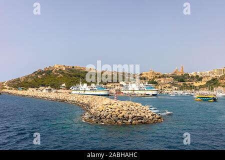 Panorama view of Gozo island of Malta from the Mgarr habor on a sunny day - Stock Photo
