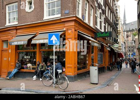 Outside of beautiful Cafe Van Zuylen Amsterdam Bar on street corner with bicycle and people sitting on window Blue one way sign with bicycle - Stock Photo