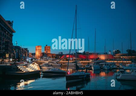 Oslo, Norway - June 24, 2019: Night View Embankment, Oslo City Hall And Moored Yachts Near Aker Brygge District. Summer Evening. Famous And Popular Pl - Stock Photo